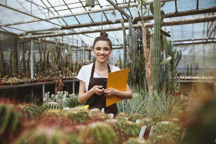 Happy young woman standing in greenhouse holding clipboard.