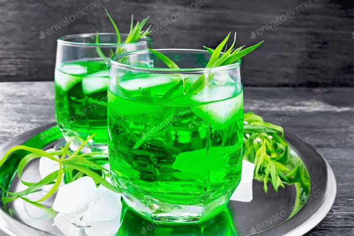 Lemonade Tarragon with ice in two glasses on wooden board