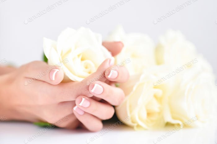 Hands of a woman with beautiful french manicure and white roses