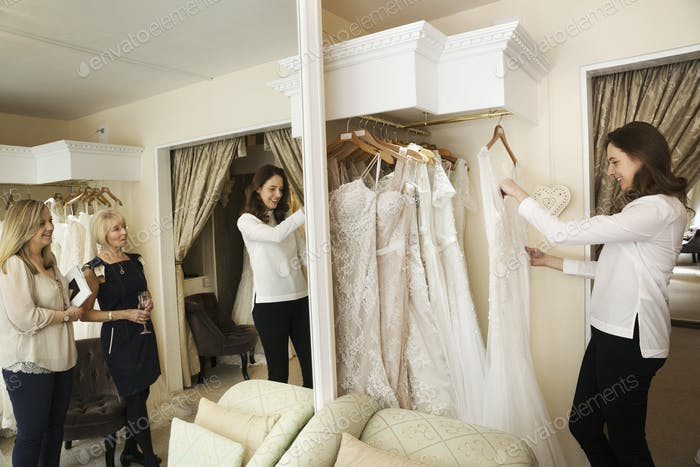 Drei Frauen, ein Kunde und zwei Einzelhandelsberater in einem Hochzeitskleidgeschäft, suchen durch die Wahl der