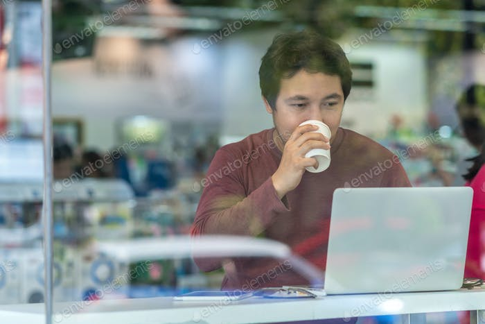 Portrait of asian businessman in casual suit drinking and using technology laptop