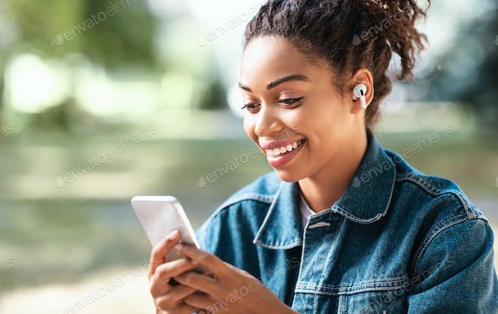 Cheerful Black Woman Using Mobile Phone And Earbuds Earphones Outdoor