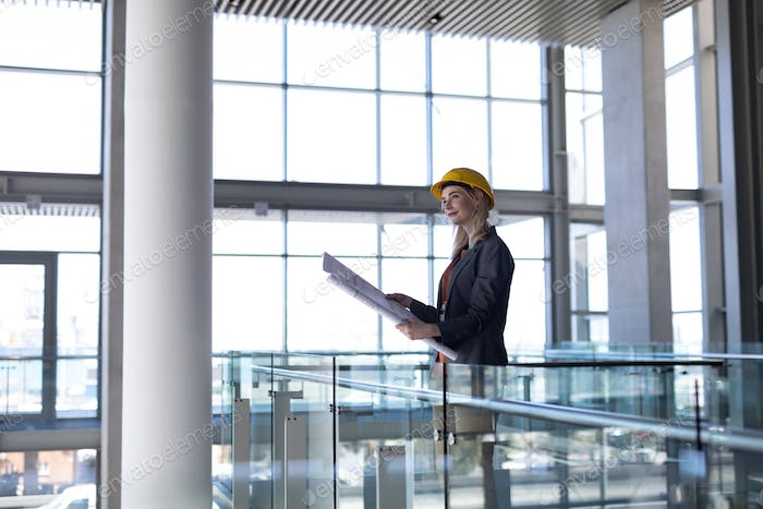 Young blonde Caucasian female architect looking at blueprint in modern office