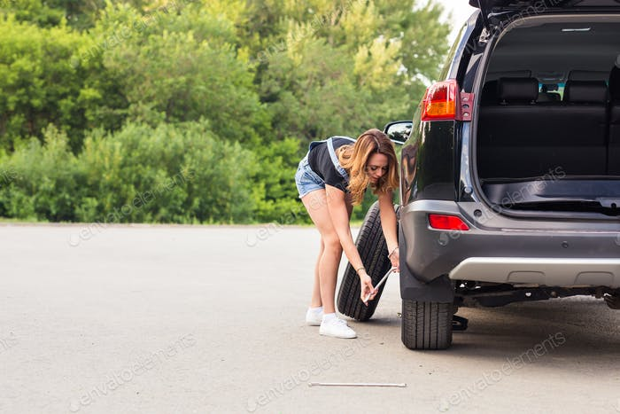 Young sexy woman repairing the car