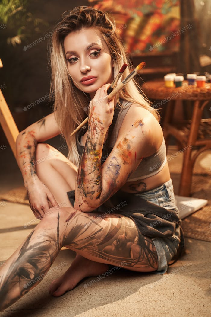 Grimy and tattooed charming woman with paintbrushes