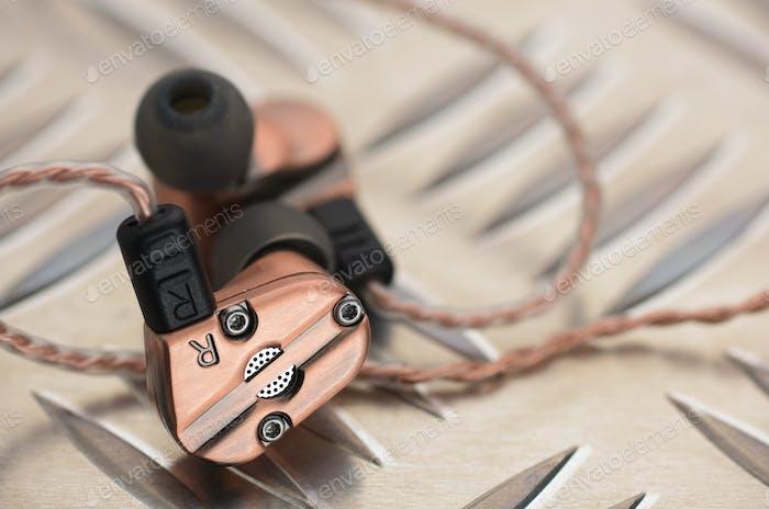 Hybrid-dynamischer Treiber ausgewogene Armaturen-Ohrhörer auf der Metallplatte.