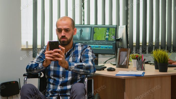Video editor in wheelchair texting on smartphone