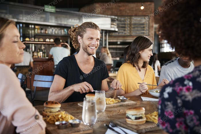 Gruppe der jungen Freunde treffen für Getränke und Essen im Restaurant