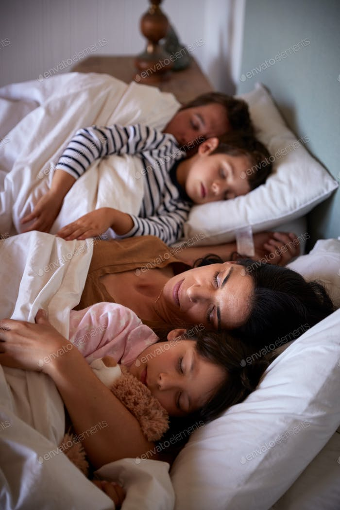 Mid adult parents and their two young children lying asleep in bed, waist up, close up, vertical