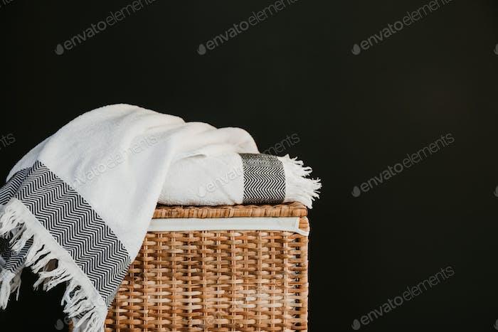 Weiße Baumwolltücher auf einer Rattanbox gegen schwarze Wand in einer Wäsche.