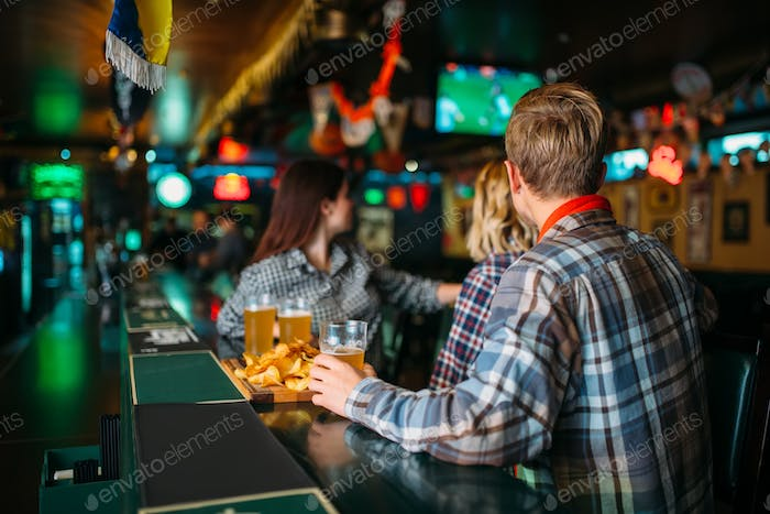 Fans with glasses of beer at counter in sports bar