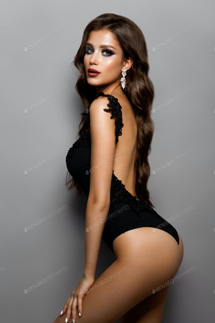 Stylish sexy girl in a black swimsuit isolated on a gray background