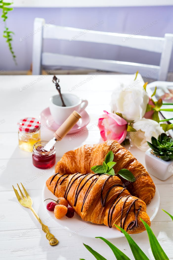 Breakfast on white wooden background - croissant, jam, berries and coffee