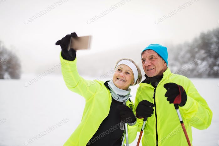 Senior couple with smartphone cross-country skiing.