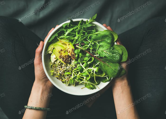 Breakfast with spinach, arugula, avocado, seeds and sprouts in bowl