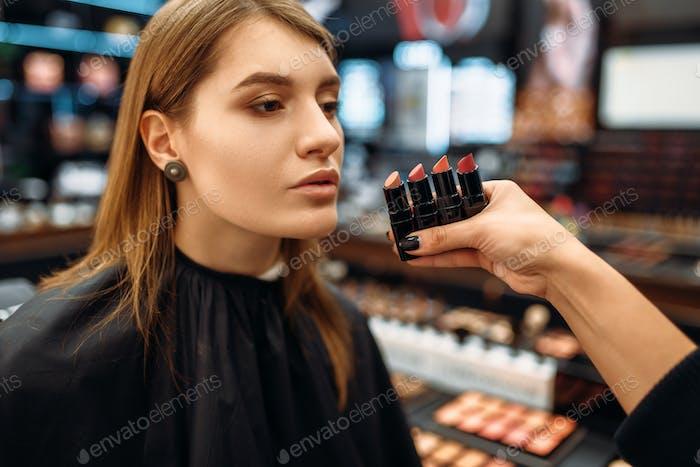 Visagiste and client chooses lipstick, makeup shop