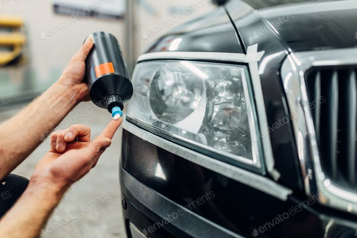 Detailing of headlight, man smears polishing paste