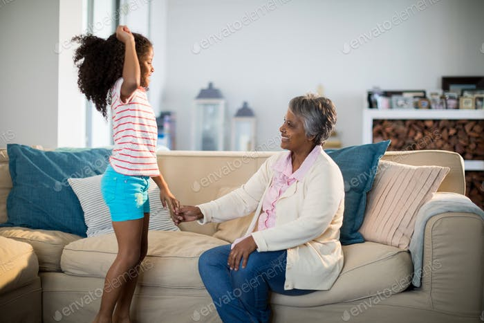 Granddaughter and grandmother having fun in living room