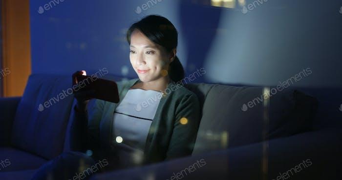 Frau Nutzung des Mobiltelefons online zu Hause am Abend