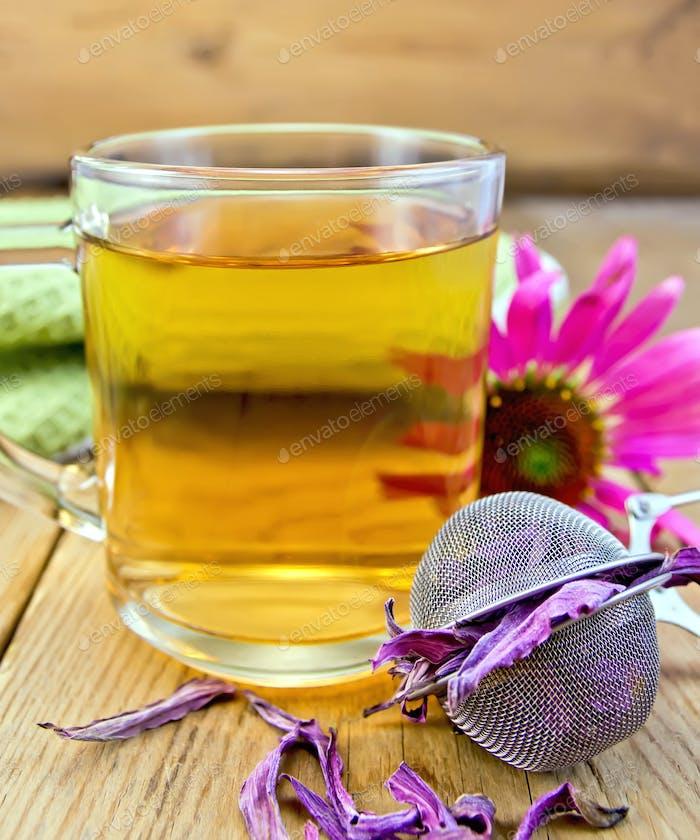 Tee von Echinacea in Glasbecher mit Sieb an Bord