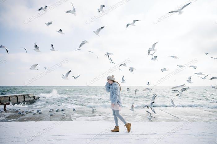 stylish young girl on winter seashore with seagulls