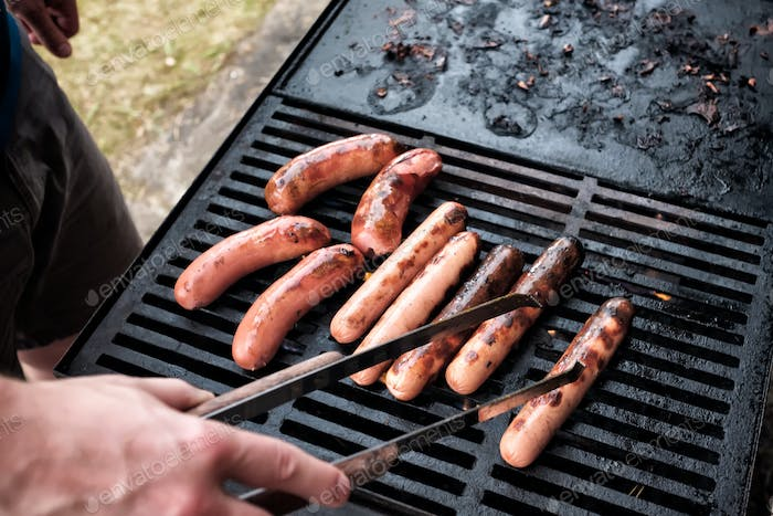 Young caucasian man hands preparing sausages on grill outdoor