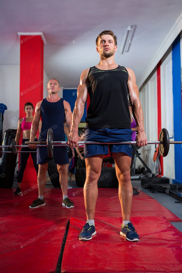 Young athletes lifting barbells on exercise mats