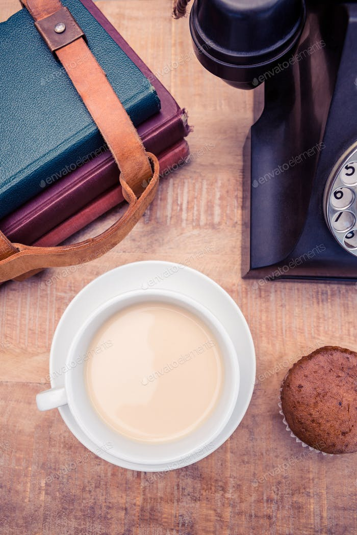 Overhead view of coffee with old landline telephone and diaries on table