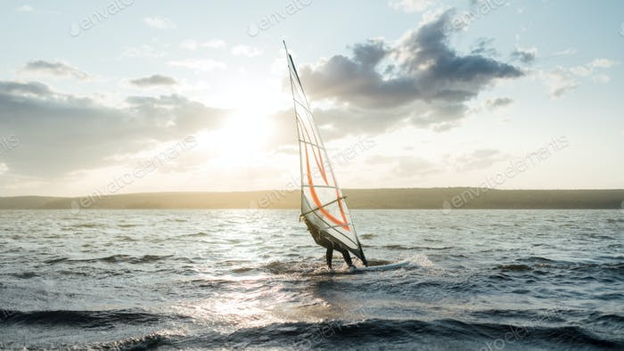 Morning windsurfing on the lake sunrise,