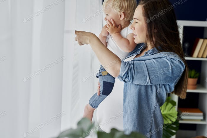 Mother and baby standing next to the window
