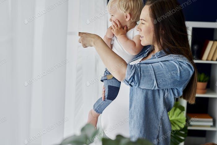 Mutter und Baby stehen neben dem Fenster