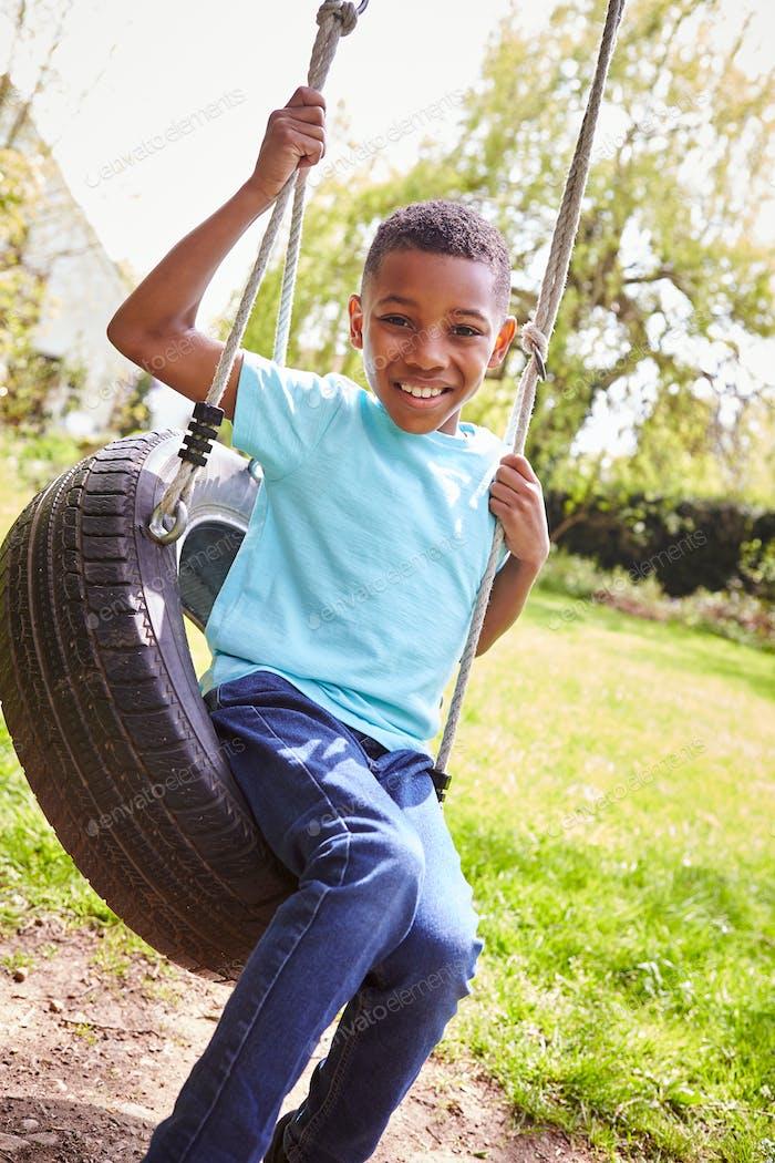 Portrait Of Smiling Boy Having Fun Playing On Tire Swing In Garden