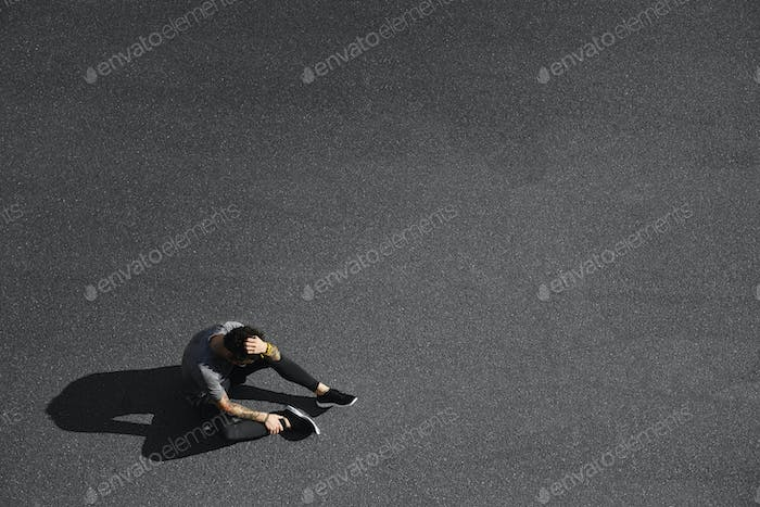 Sport fitness man relaxing after training. Young male athlete resting sitting in asphalt after runni