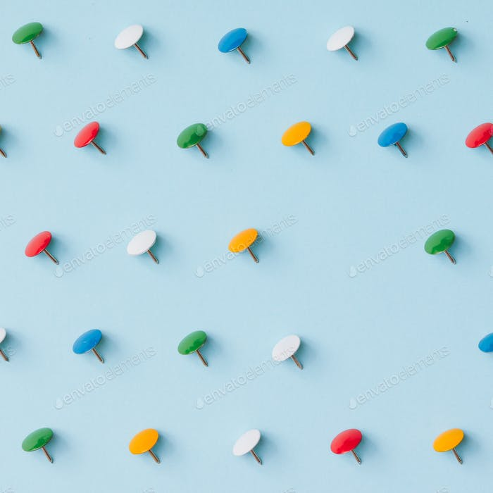 Colorful pins on blue background. Minimal concept.