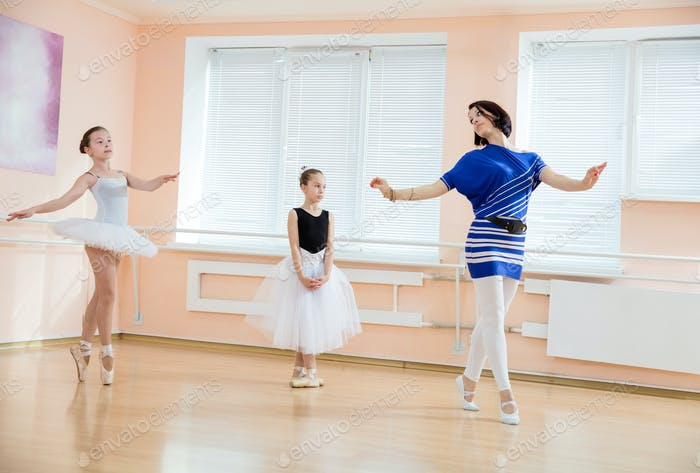 Ballet teacher and young students at dance class