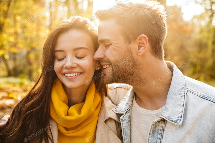 Image of attractive young caucasian couple walking through autumn park