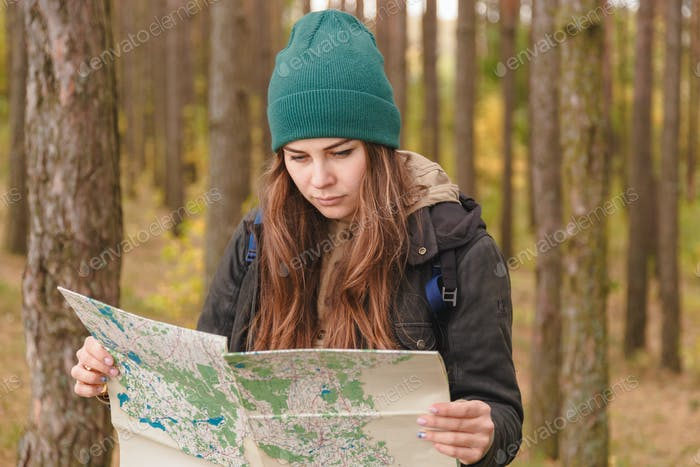 woman with travel map and backpack in pine forest