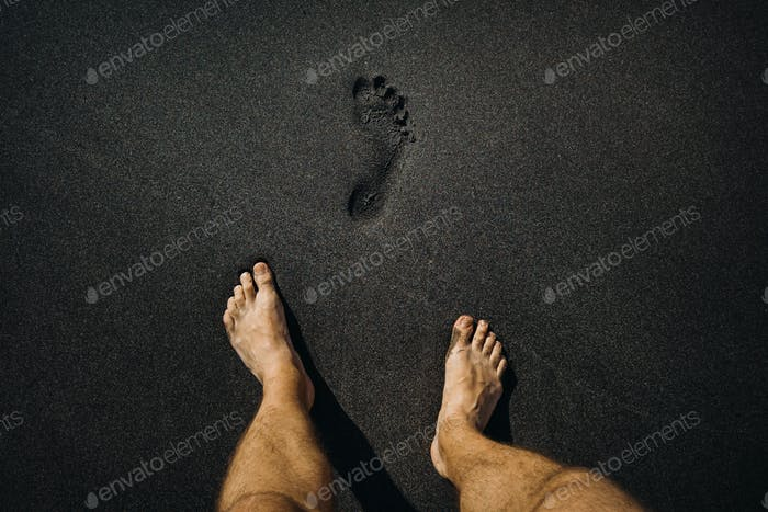 Close up of male footprints and feet walking on the volcanic black sand on the beach