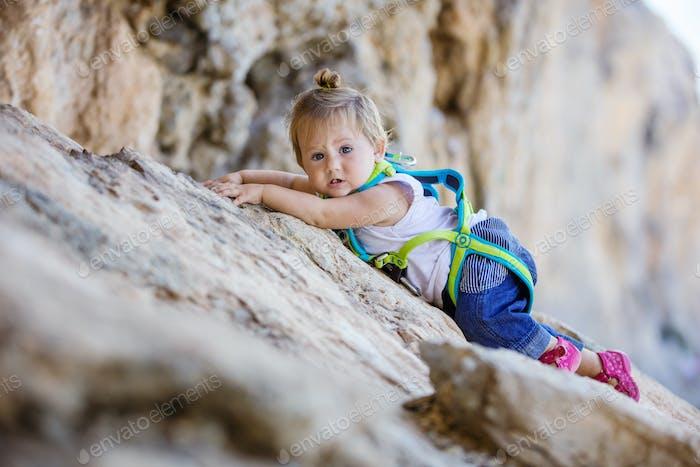 Little girl climbing up cliff