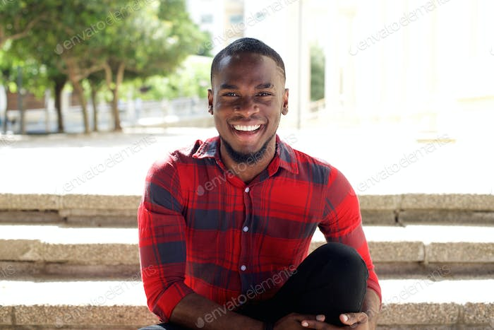 Smiling young african man sitting on steps outdoors
