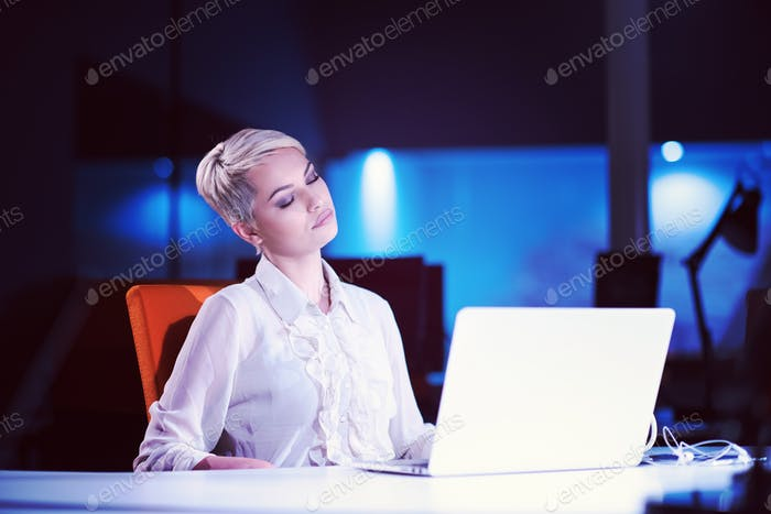 woman working on laptop in night startup office