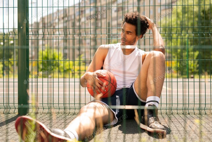 Young relaxed active man with ball sitting by fence of basketball court