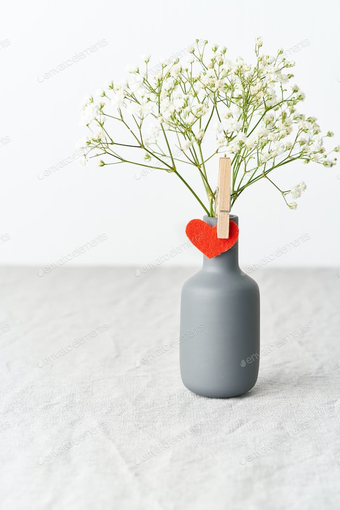 Valentine's Day. Delicate white flowers in a vase. Red felt heart - symbol of lovers.