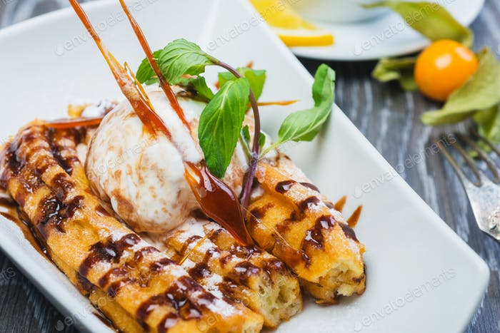 Delicious Dessert Eclair with Caramel and Ice Cream with a cup of tea on a wooden table