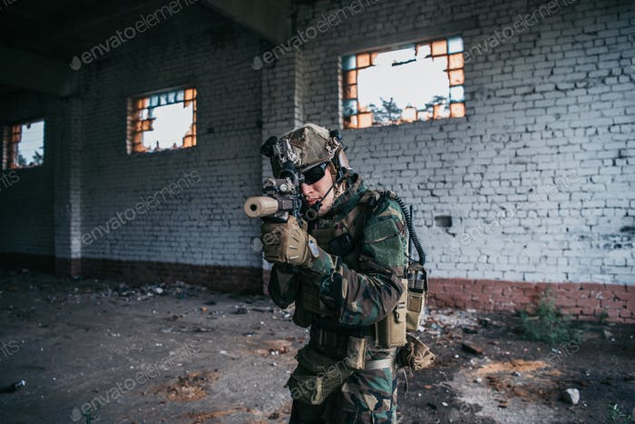 Special forces soldier walking with aimed assault rifle in destroyed building