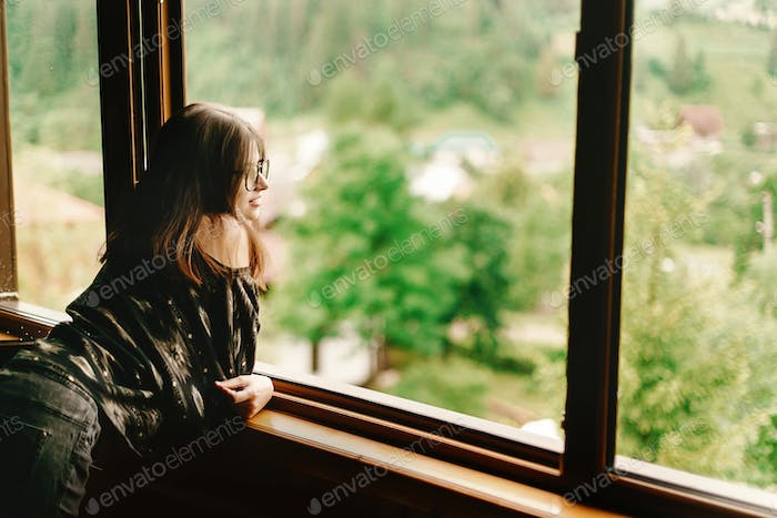 Stylish hipster woman sitting at window with amused smile  in wooden house