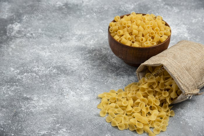 Pasta in a rustic basket and in a wooden bowl