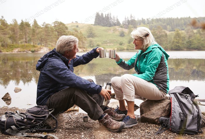 Senior couple sitting by a lake drinking coffee during camping holiday making a toast with mugs