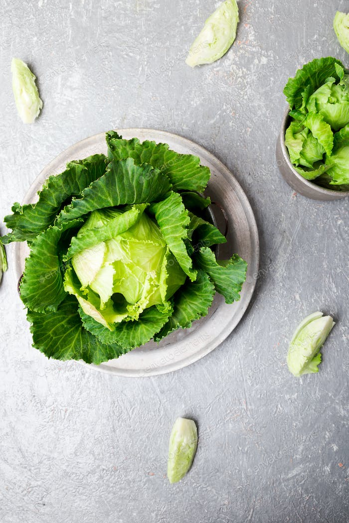 Fresh green cabbage in metal plate on grey background. Top view. Copy space.