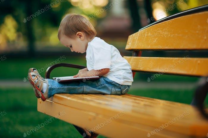 little reading boy in summer park